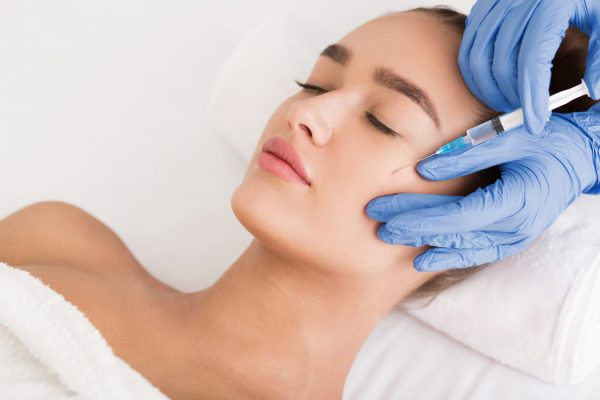 Beauty procedure. Woman receiving hyaluronic acid injection in spa salon