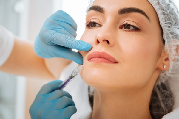Facial procedure. Nice beautiful woman having an injection in her face while fighting with age
