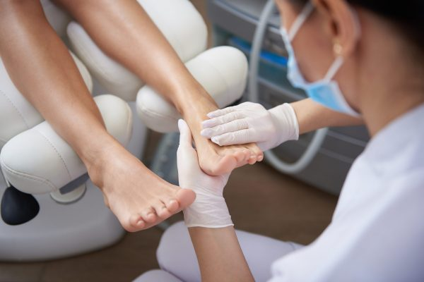 Close up of female hands in white sterile gloves holding lady foot